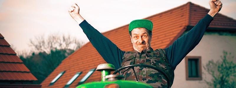 Mann jubelt auf Traktor